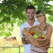 Couple with a basket of fruits — Stock Photo