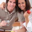 Stock Photo: Married couple having breakfast in kitchen
