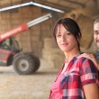 Stock Photo: Agricultural couple in the barn with a tractor