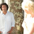 A man posing and a blonde woman hidden behind a tree watching him in secret — Stock Photo #7931298