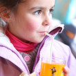 Little girl drinking orange juice through a straw — Stock Photo