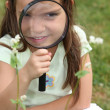 Girl with magnifying glass — Stock Photo