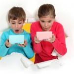 Children playing handheld computer games — Stock Photo