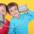 Kids having phone call with tin cans on yellow background — Stok Fotoğraf #7931834