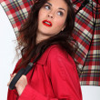 Woman in a red coat with a tartan umbrella — Stockfoto