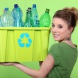 Stock Photo: Womrecycling crate of plastic bottles