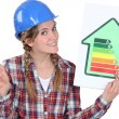 Stock Photo: Craftswoman holding an energy consumption label