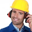 Happy builder wearing ear protection — Stock Photo