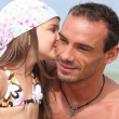 Stock Photo: Girl giving dad a kiss