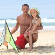 Man and little girl playing with kite at the beach — Stock Photo #7933737