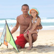 Man and little girl playing with kite at the beach — Stock Photo