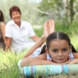 Little girl relaxing in park with mother and grandma in background — Stock Photo #7933805