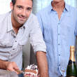 Stock Photo: Two men cutting celebration cake