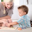 Stock Photo: Mother and son doing a jigsaw puzzle