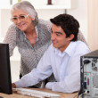 Young man helping his grandma with her computer. — Stock Photo