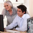 Young man helping his grandma with her computer. — Stock Photo #7933979