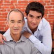 Teenager and his grandfather posing in restaurant — Stock Photo #7934065