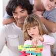 Parents looking her daughter playing with blocks — Stock Photo