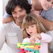 rodiče hledají její dcera hraje s bloky — Stock fotografie
