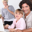 Parents and little girl with laptop — Stock Photo