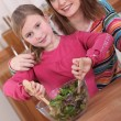 Young woman and little girl mixing a green salad in a bowl — Stock Photo