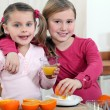 Two little girls making orange juice. — Stock Photo