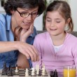A mother and her daughter playing chess. - Stock Photo