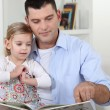 Stock Photo: Father reading story to his daughter