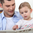 Stock Photo: Father and his little girl reading a book