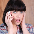 Shocked woman with mobile telephone — Stock Photo
