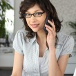 Young businesswoman using a phone and laptop — Stock Photo