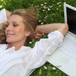 Foto Stock: Pretty lady lounging in grass next to laptop computer