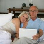 Senior couple on a sofa with laptop computer — Stock Photo