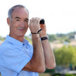 Mature man with binoculars. - Stock Photo