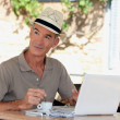 Stock Photo: Senior with laptop outside cafe