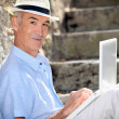Retired man sat against stone wall with laptop — Stockfoto