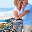 Mature couple with bikes by a beach — Foto Stock