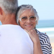 Elderly couple hugging by a beach — Stock Photo #7935468