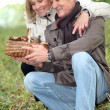 Stock Photo: Old couple watching a wickerwork basket of mushrooms in the countryside