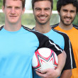 Three smiling young football players — Stock Photo