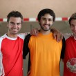 Three young men indoors with hand ball — Stock Photo