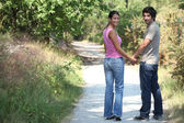 Couple outdoors walking hand in hand — Stock Photo