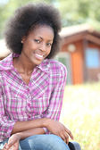 Woman in pink checked shirt sitting in front of wooden cabin — Stock Photo