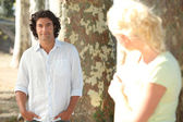 A man posing and a blonde woman hidden behind a tree watching him in secret — Stockfoto