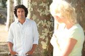 Un uomo in posa e una donna bionda, nascosto dietro un albero, guardando lui in segreto — Foto Stock