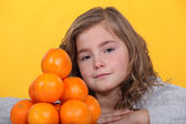 Little stood with pile of oranges — Stock Photo