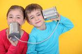 τα παιδιά, έχοντας μια τηλεφωνική κλήση με τσίγκινα δοχεία σε κίτρινο φόντο — Φωτογραφία Αρχείου
