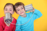 Kids having a phone call with tin cans on yellow background — Stok fotoğraf