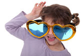 Young girl wearing oversized heart-shaped glasses — Stock Photo