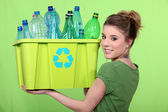 Woman recycling crate of plastic bottles — Stock Photo